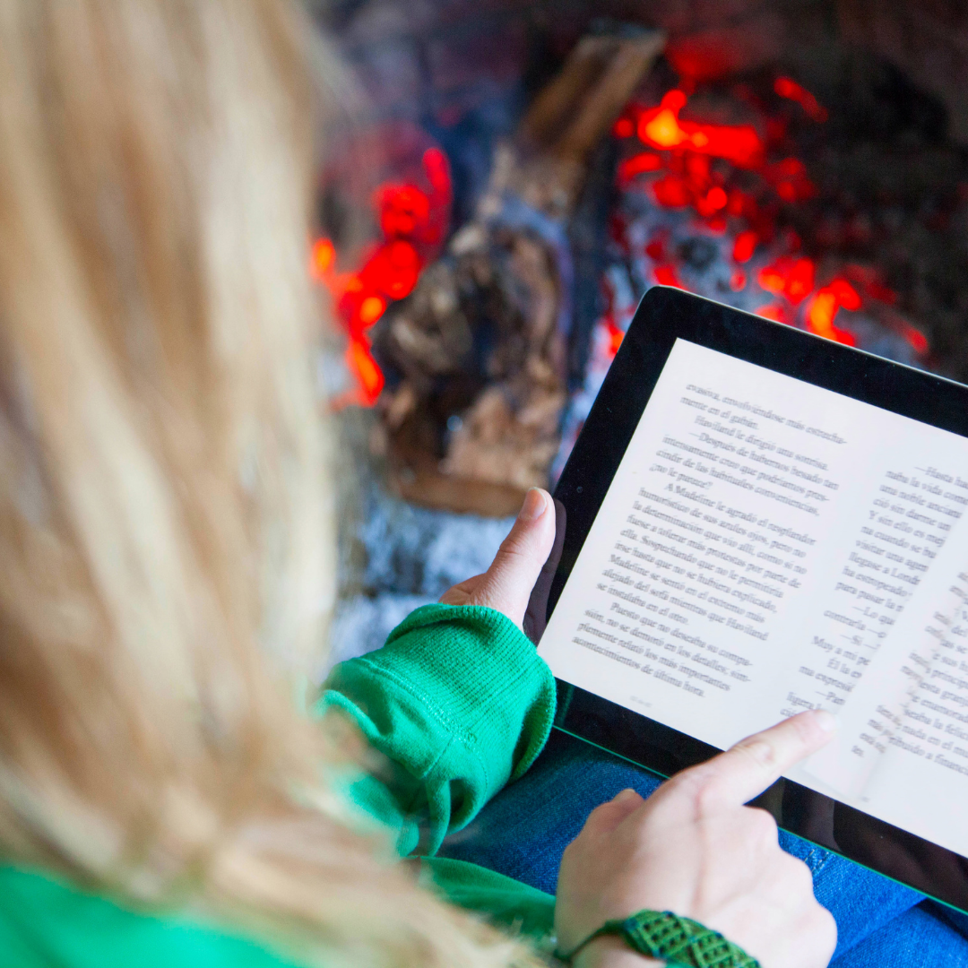 Person reading an eBook on a tablet near a fire
