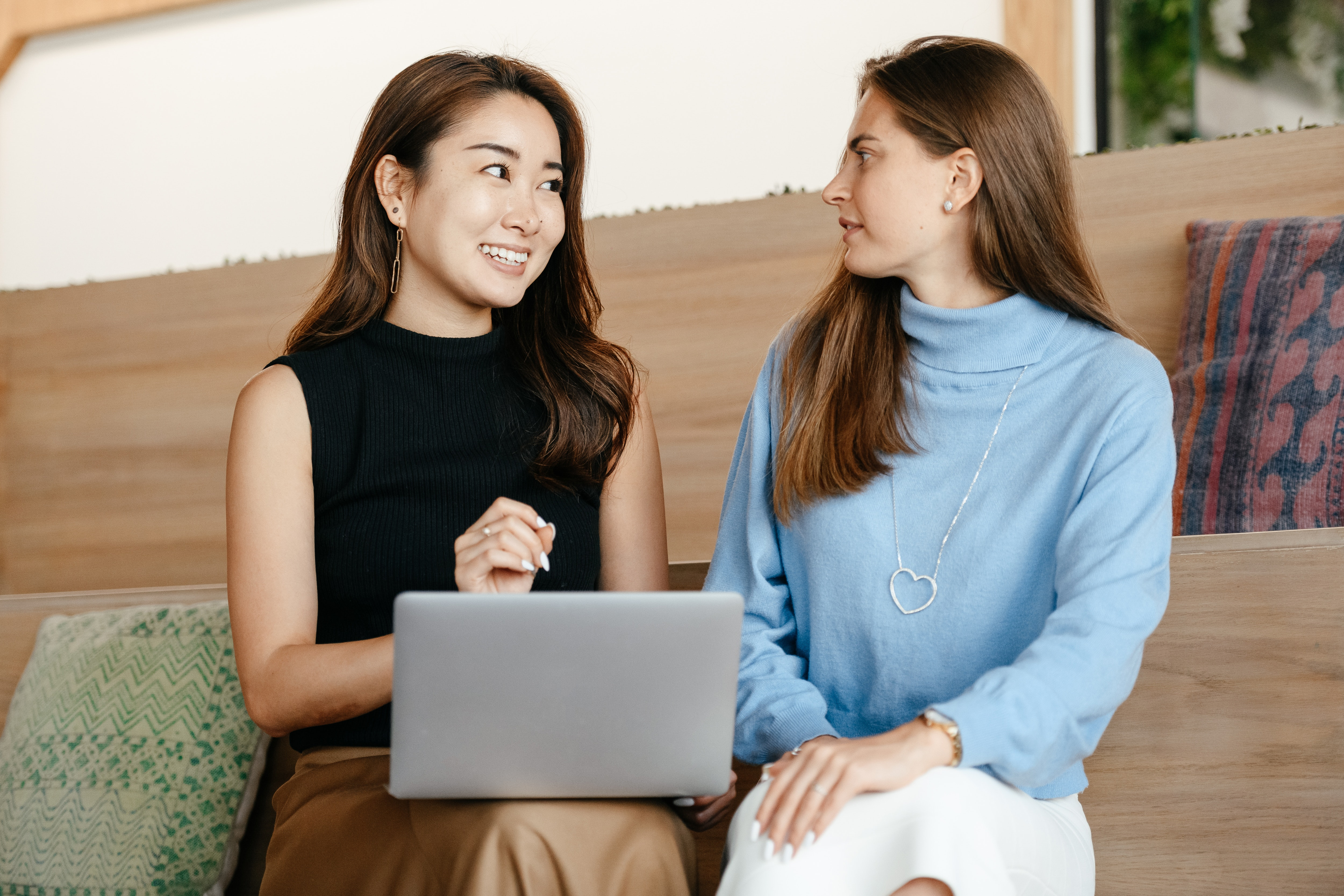 Content cheerful diverse women talking and using laptop