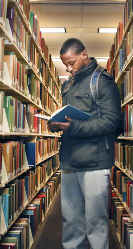 black, male student reading a book standing in the library stacks