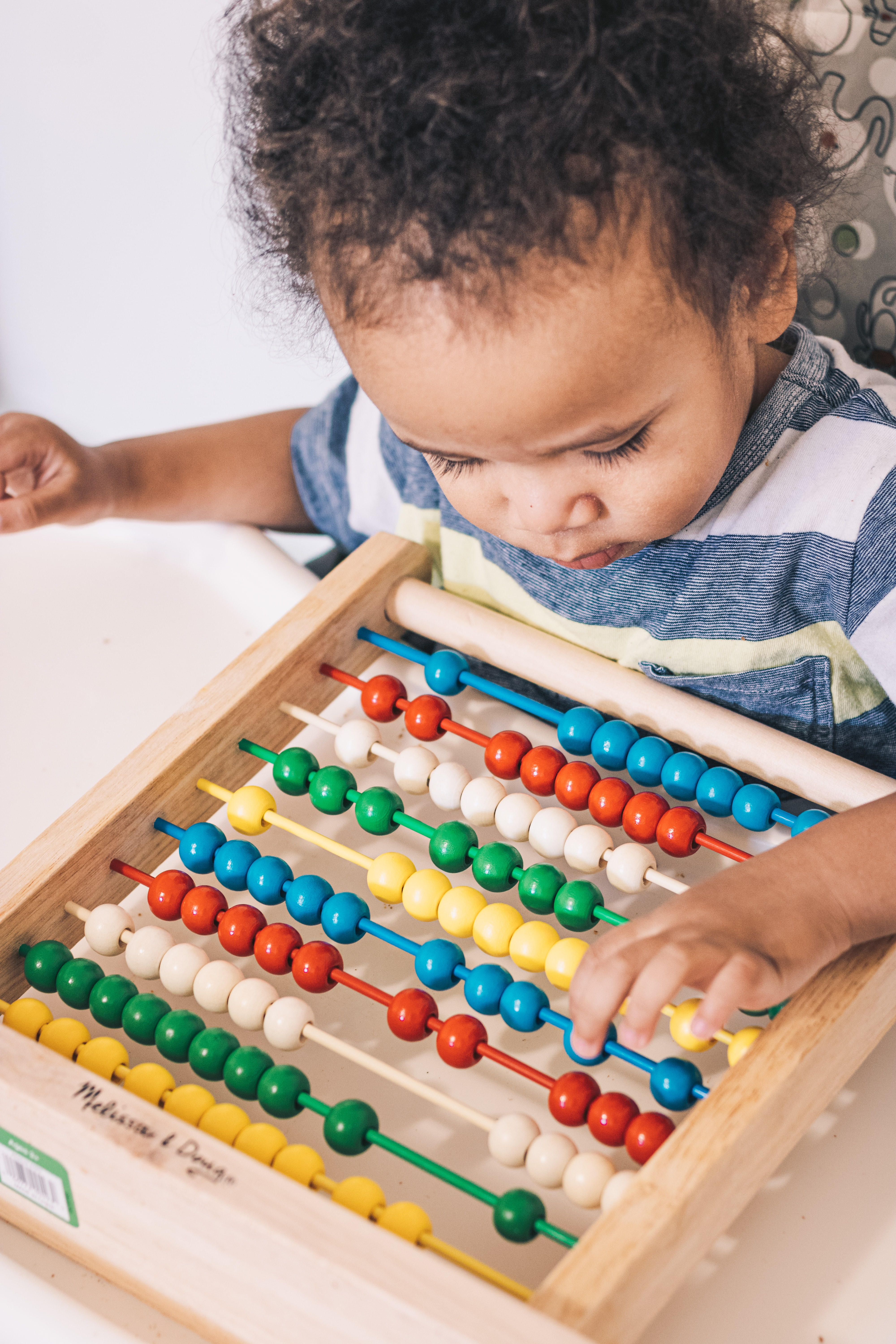 Toddler playing with abacus.