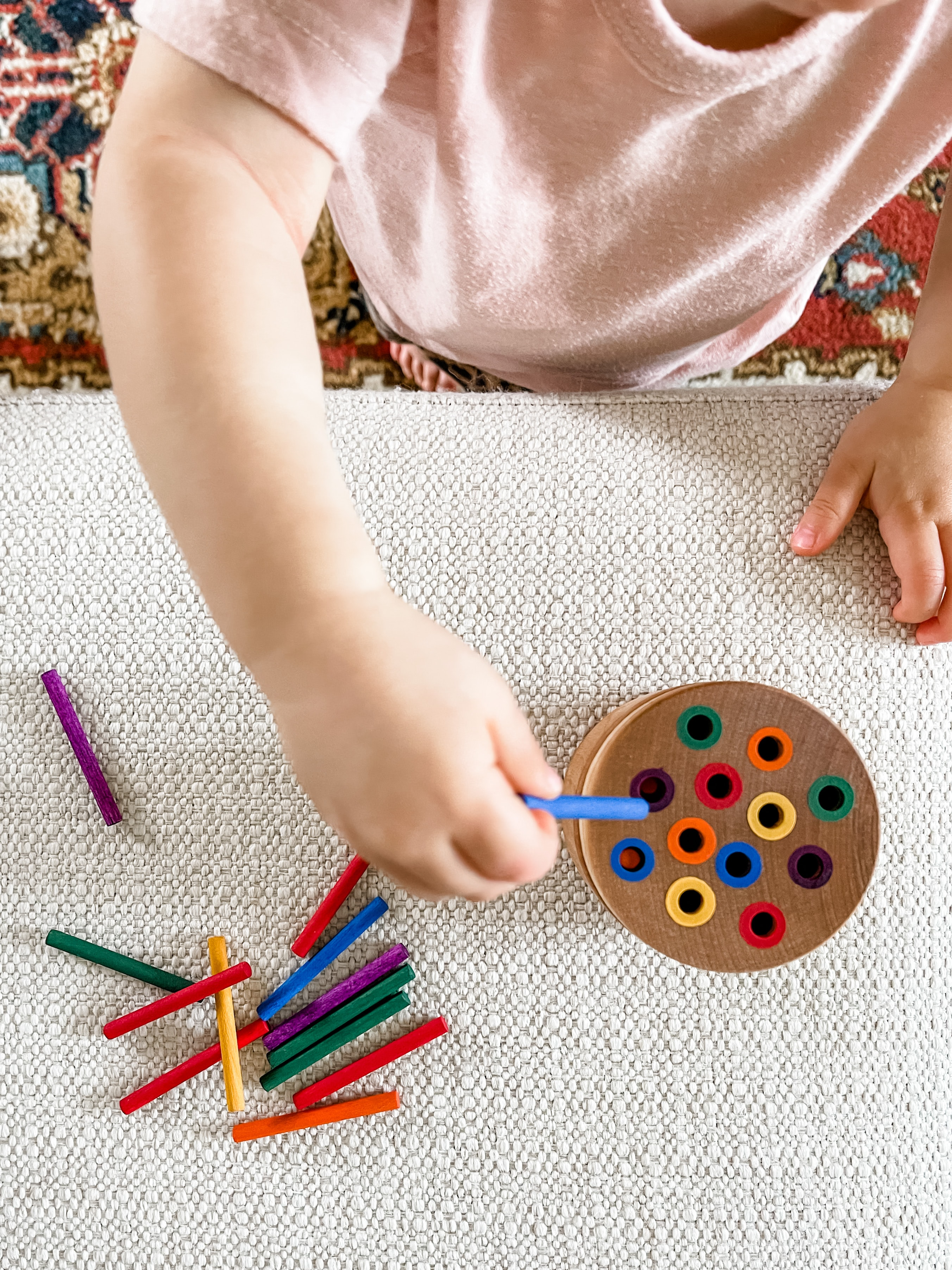 Toddler playing with a toy to match colored sticks into a colored hole.