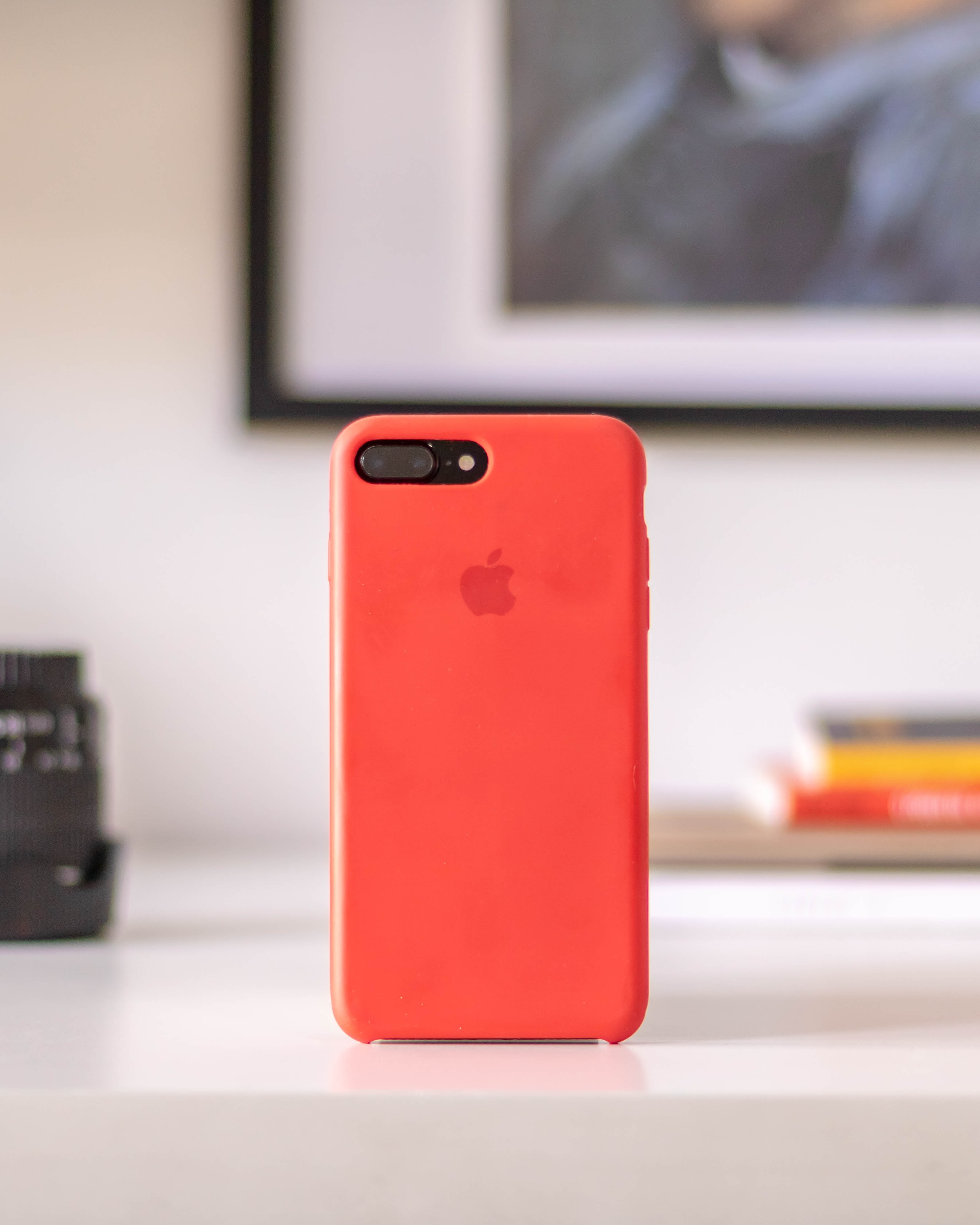 iPhone with red case on a table.