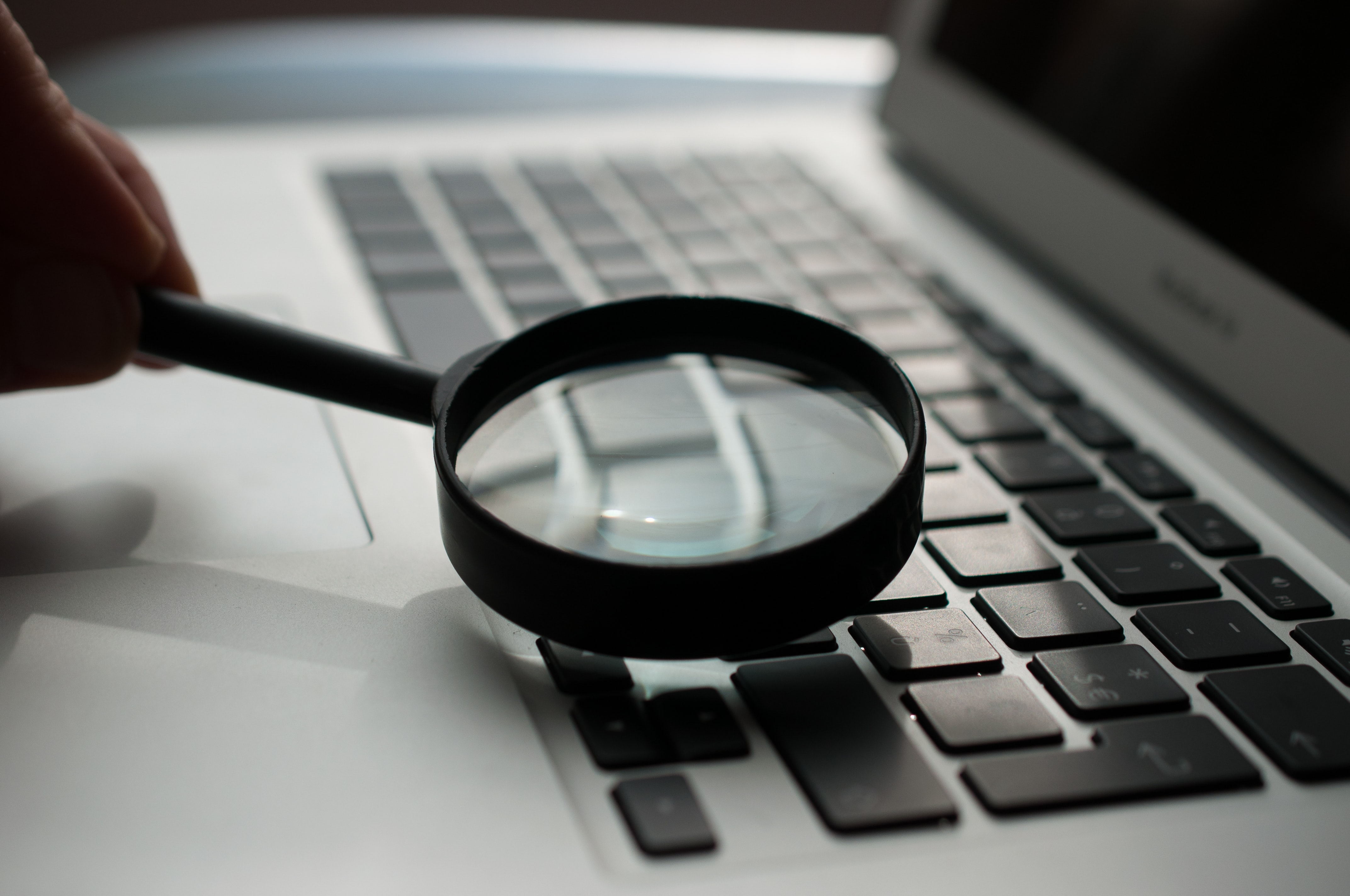 Magnifying glass resting on top of a laptop keyboard