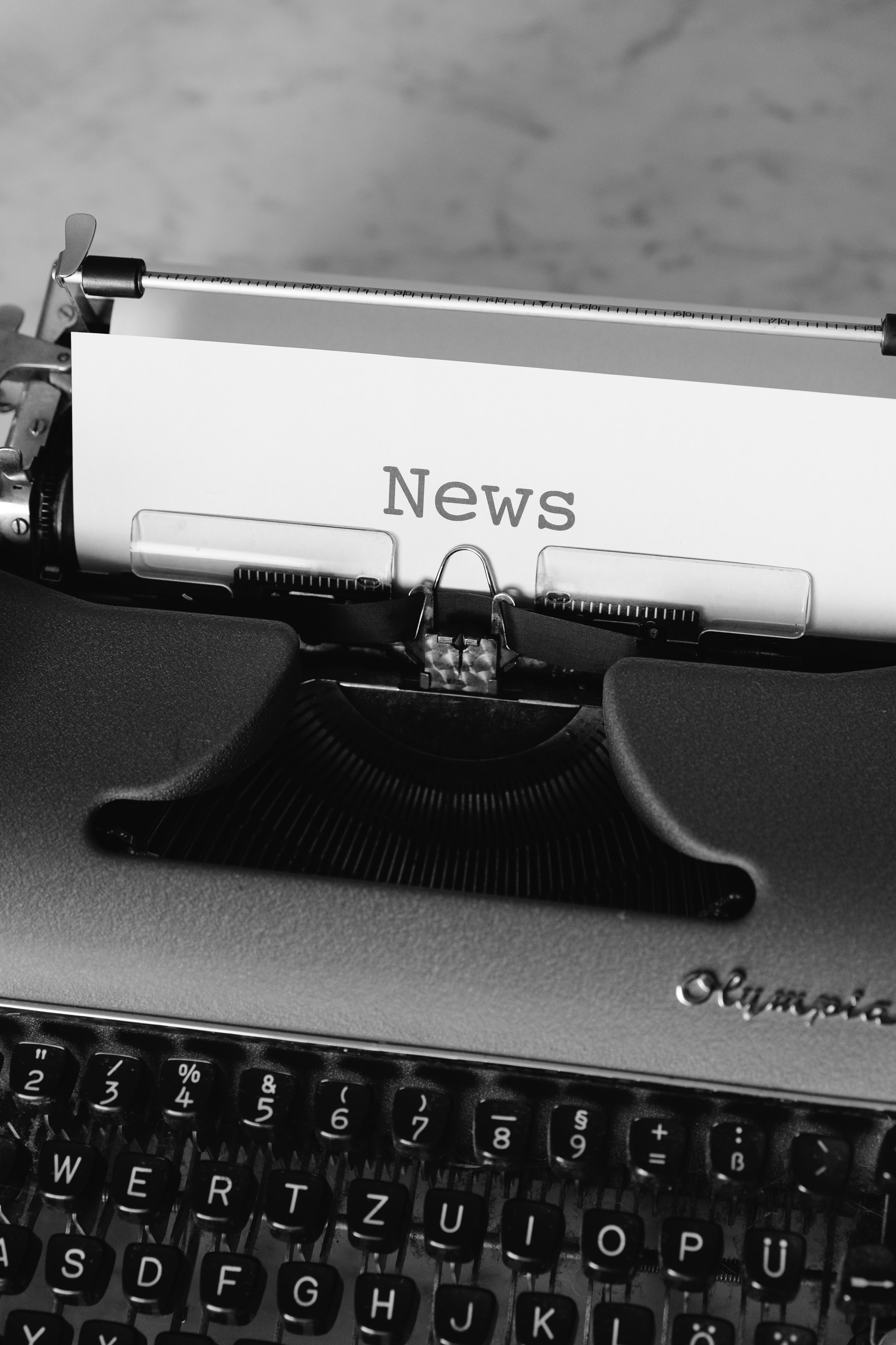 """Typewriter with paper inside that says """"News"""""""
