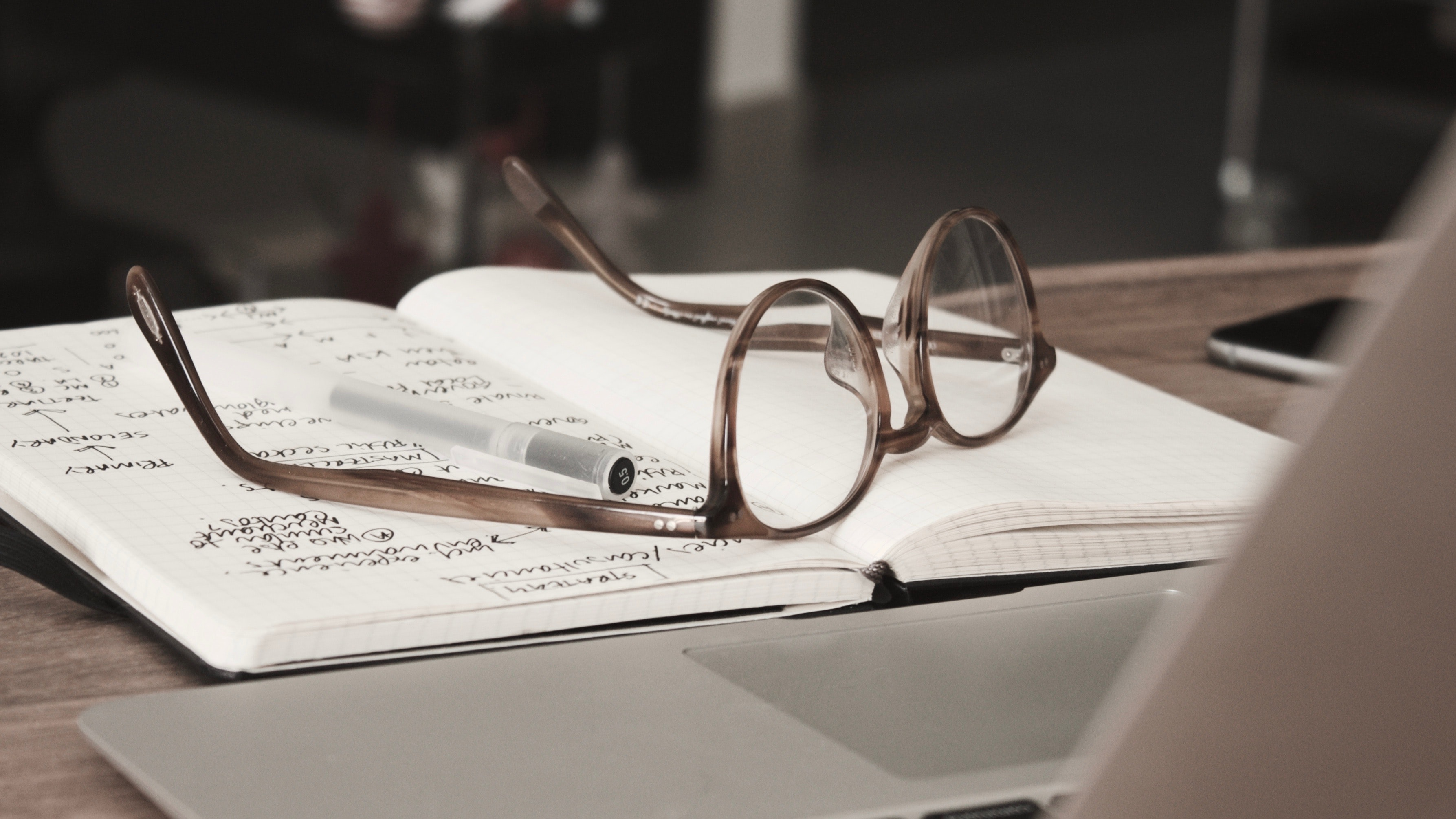 A pair of glasses resting on top of an open notebook.