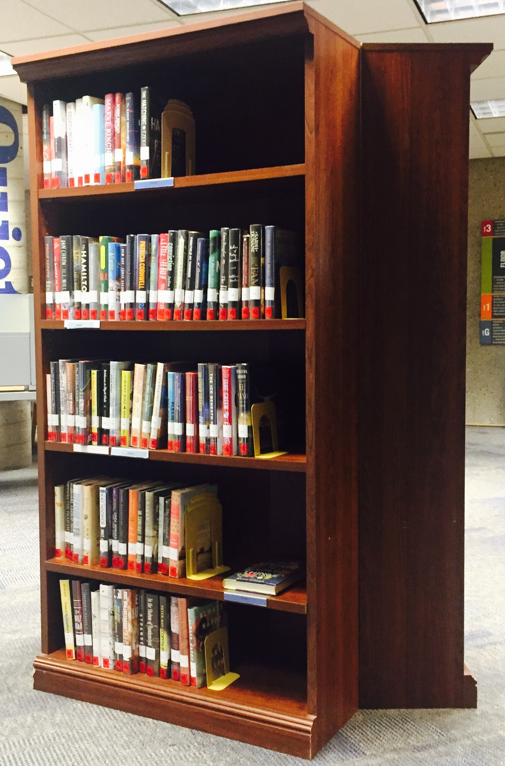 The Popular Reading shelf is on the second floor, at the top of the main stairwell.