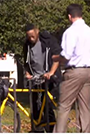 A black man and a white man in a park looking at a bike in a bike rack