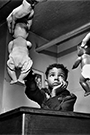 A black child playing with a white doll and a black doll while a man looks on
