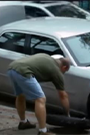 A man changing a tire with a woman watching