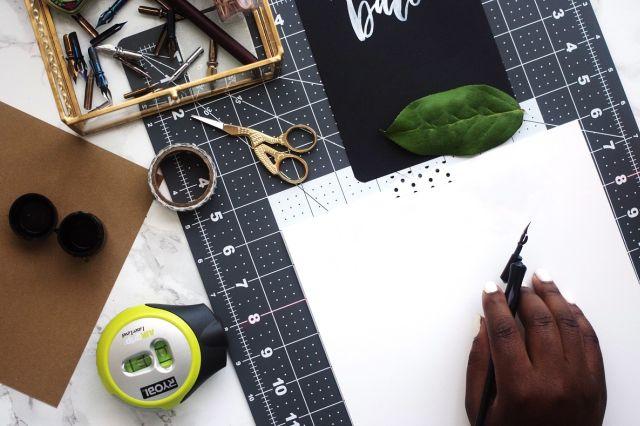 An image of a cutting mat, scissors, ink, paper,