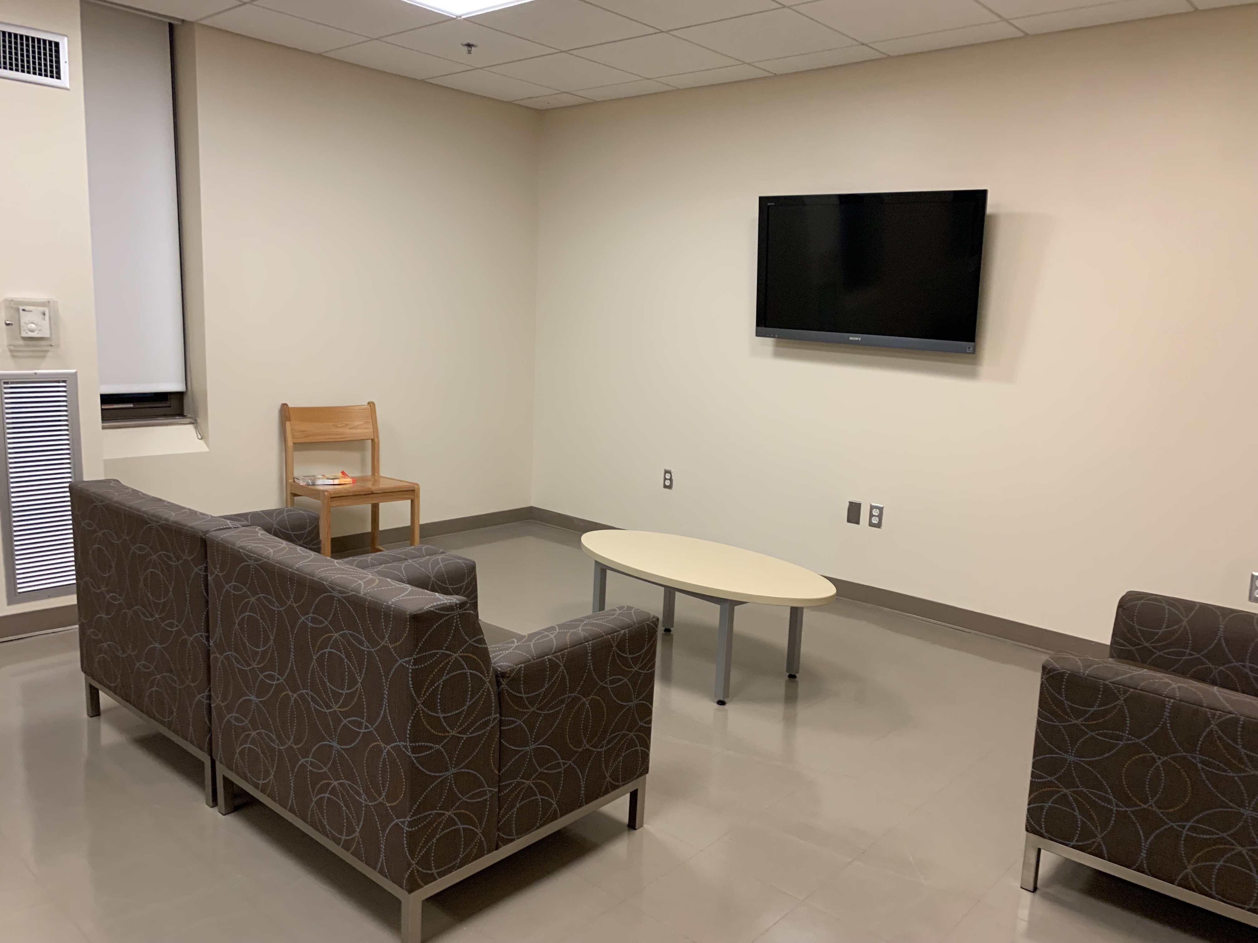 small lounge with couch, arm chair, table, and wall-mounted TV