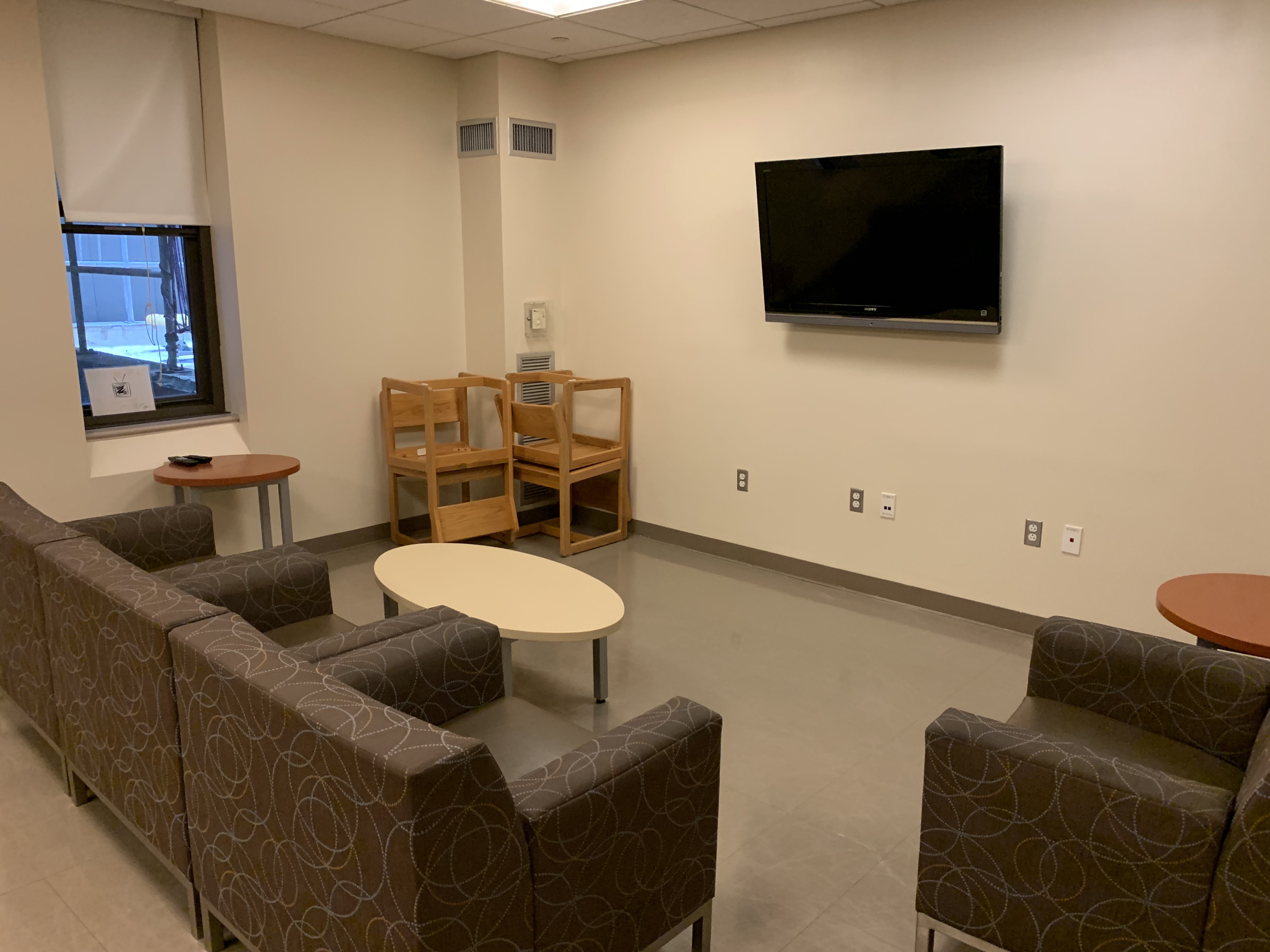 small lounge with 4 arm chairs, table, and wall-mounted TV