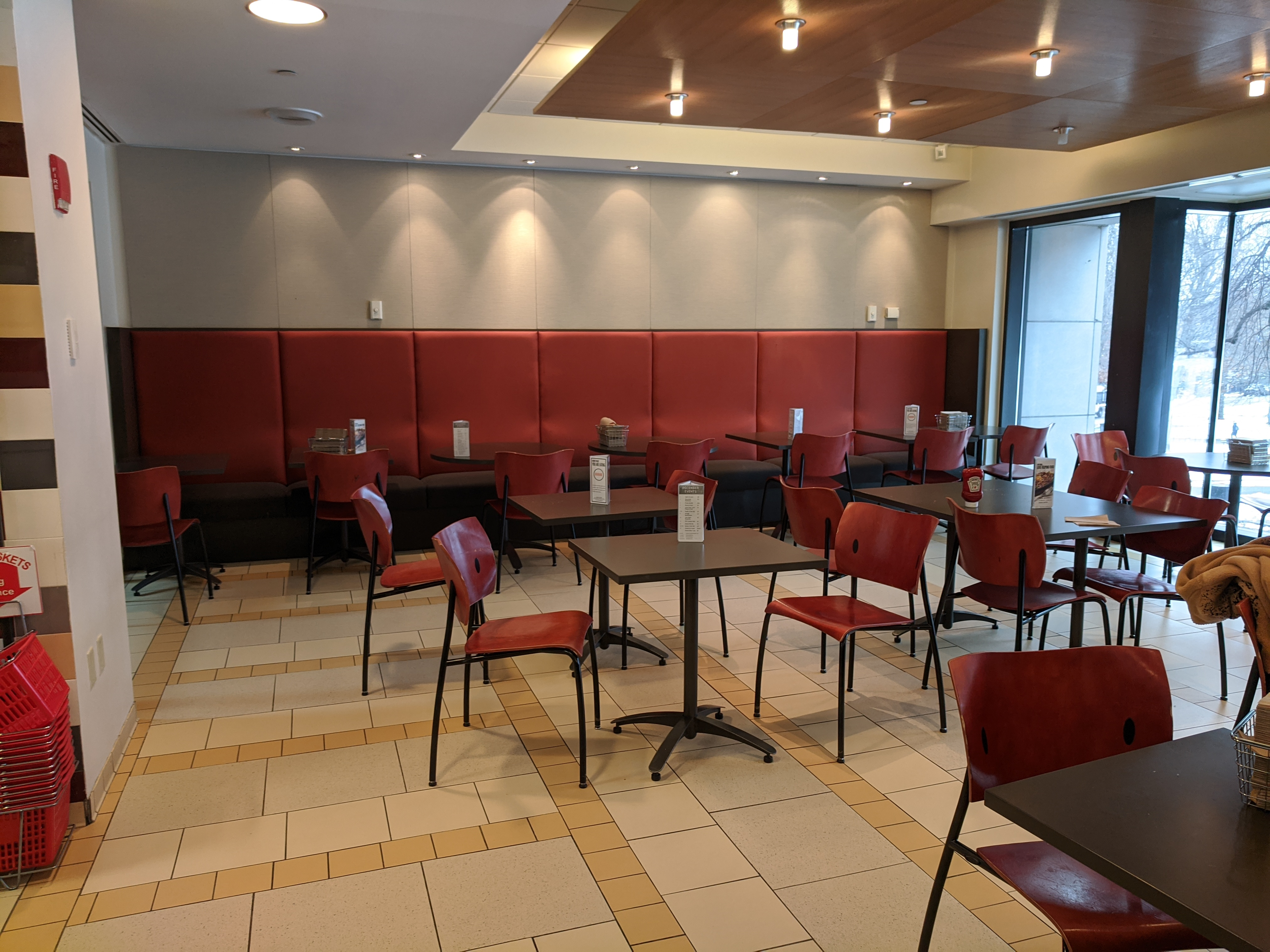 cafe with red banquette, about 12 red chairs, and 4 small tables