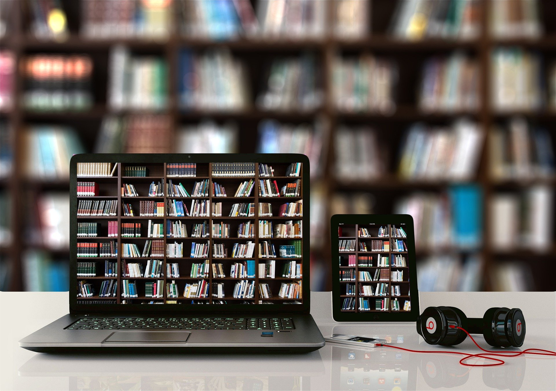 Laptop and tablet with bookshelves on the screens