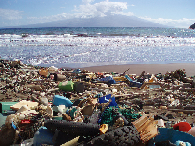 large pile of trash and debris on a beach