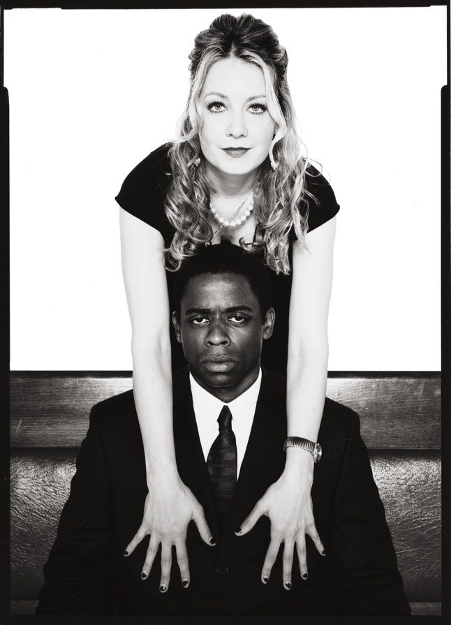 Black man sitting in front of standing White woman