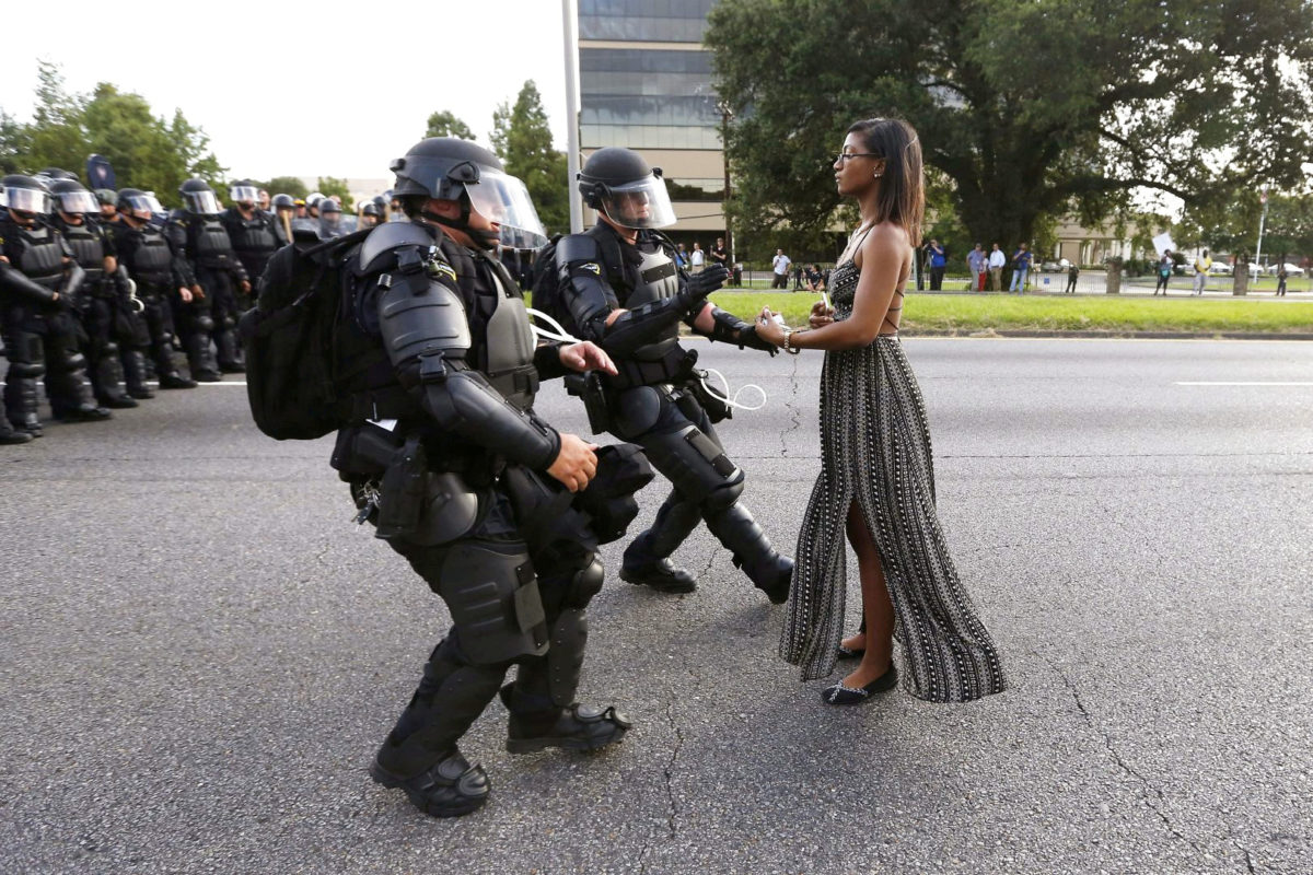 police in military gear and young Black woman stand facing each other
