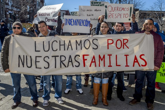photo of people standing at protest with signs in Spanish