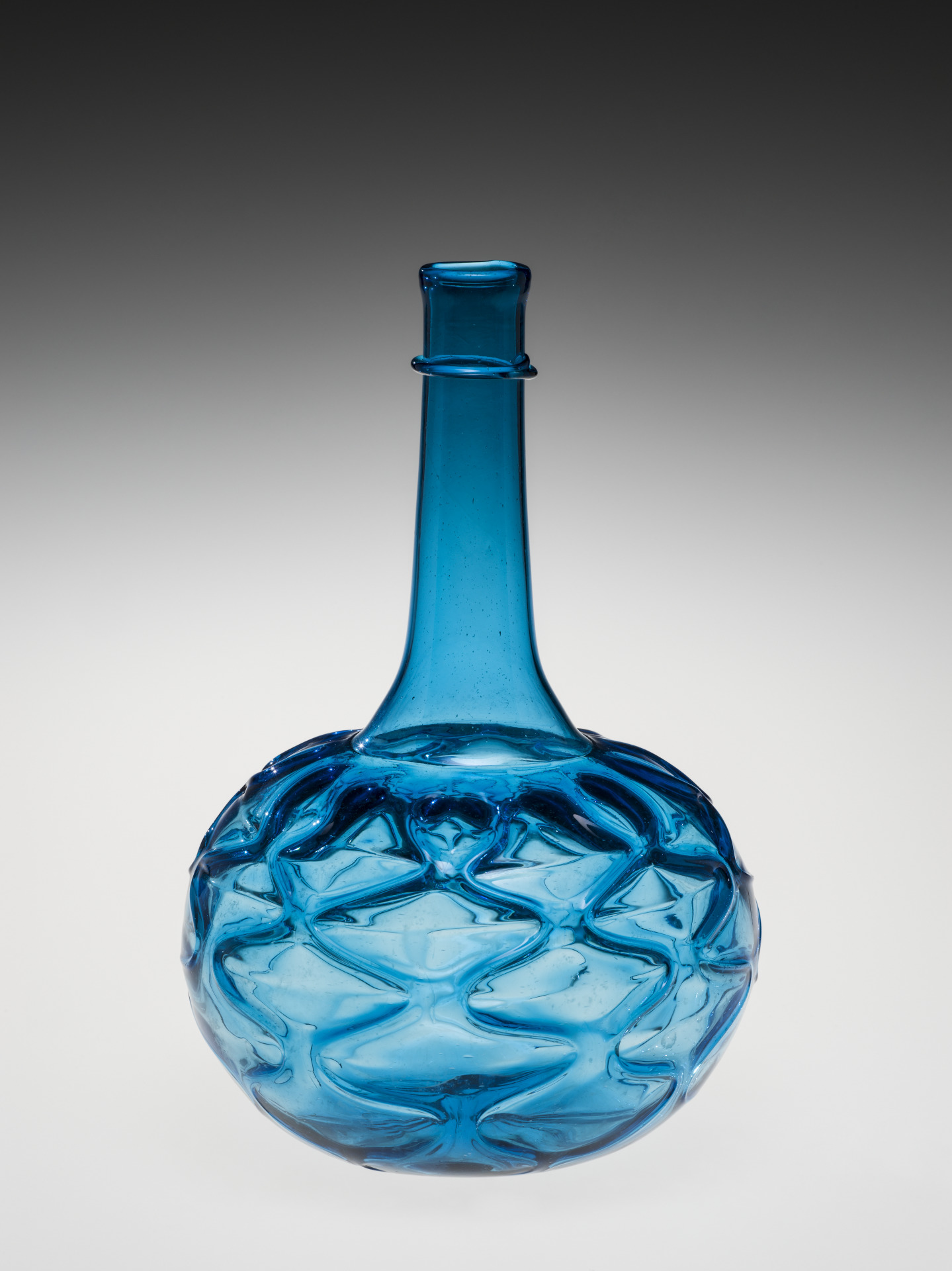 Light blue glass; blown, tooled, applied. The carafe or decanter consists of a mold-blown and tooled bulbous body with kicked base, a narrow shoulder, and a long, straight-sided neck. The body is tooled into a pattern of