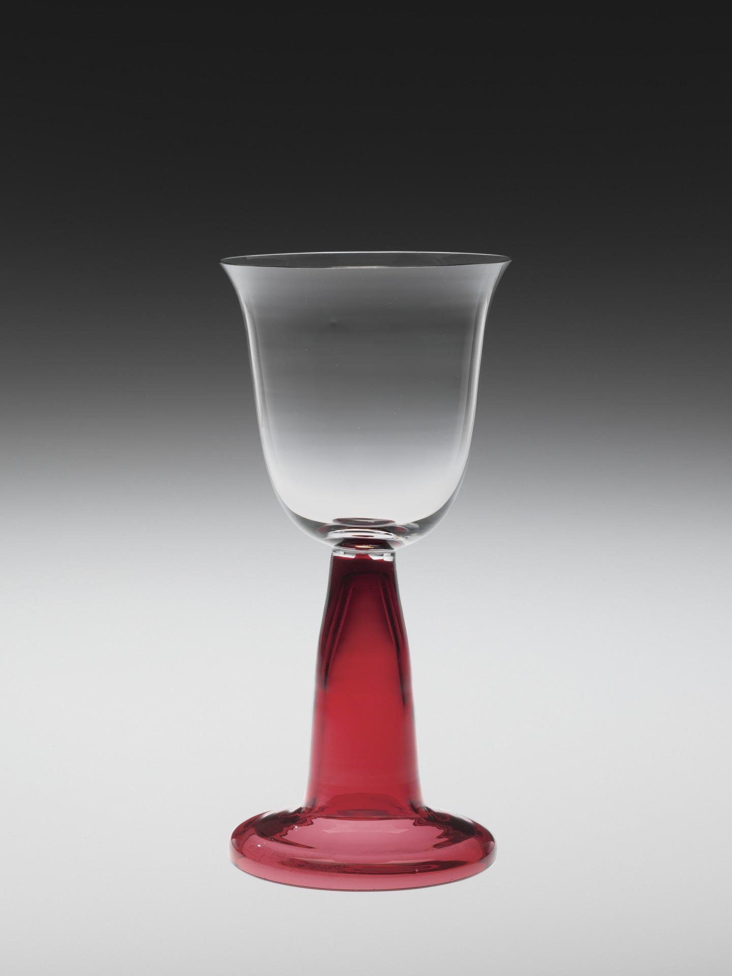 Colorless and transparent ruby glass; blown, tooled, applied. Colorless bowl with flared rim sits atop a red, open cylindrical, stem that widens slightly to domed foot.