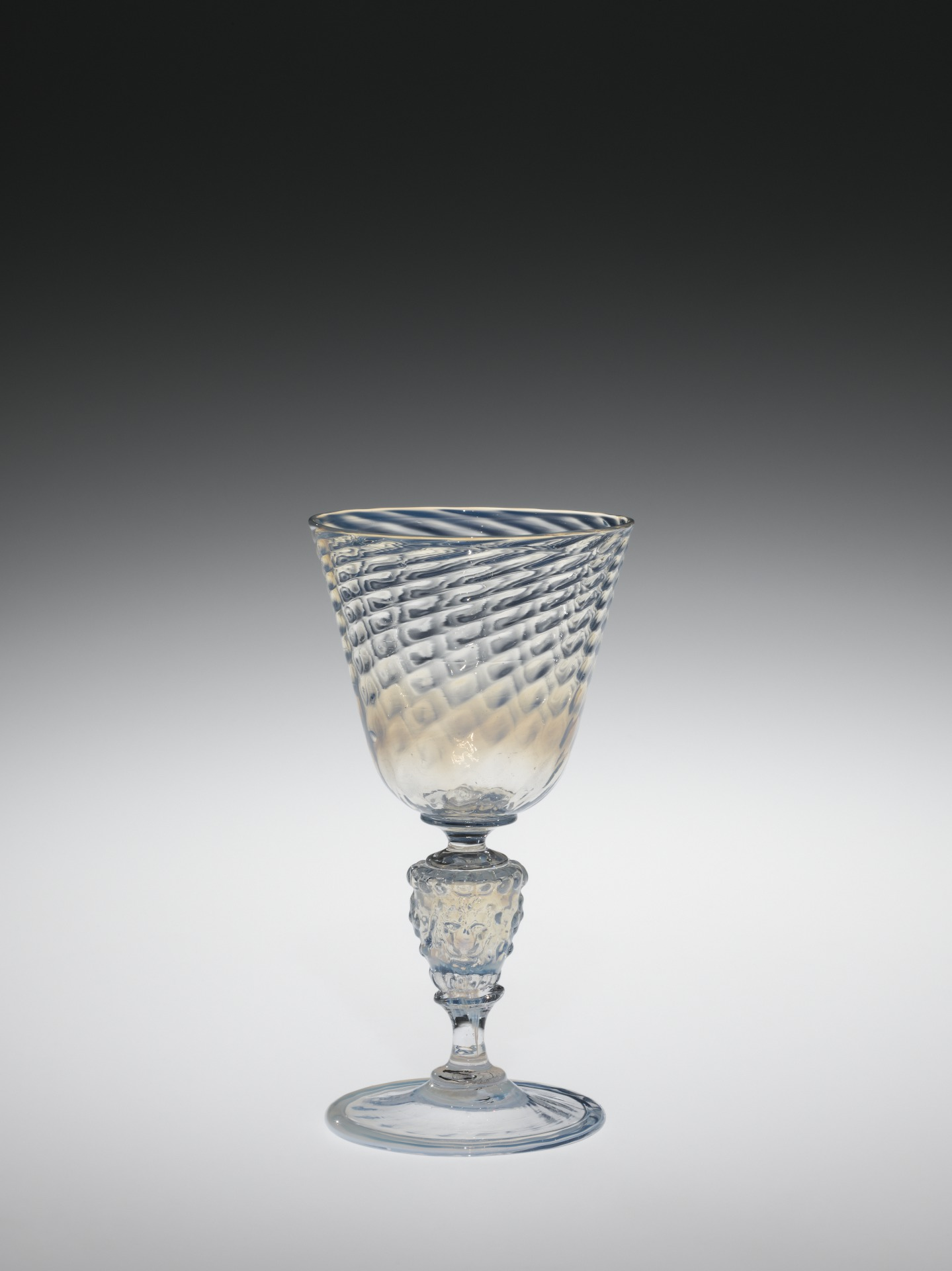 Goblet with conical optic-molded cup and foot joined with a stem consisting of a hollow molded lion mask flanked on top and bottom with waisted elements.