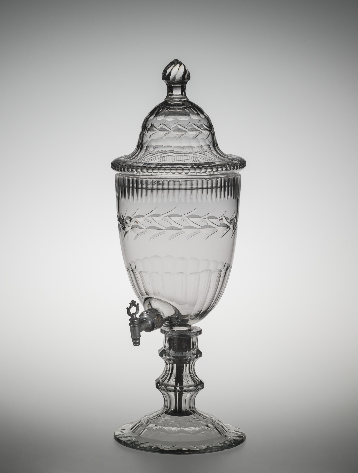Dark colorless lead glass; blown and cut. (a) Deep ovate bowl having on one side, at bottom, a cylindrical nozzle fitted with pewter spigot set in cork, and at bottom a metal mounting and rod passing through knopped stem of standard with domed circular foot; decoration: circlet of trifoliate leaves on plain field between bands of broad paneling at bottom and finger-flutes at top. (b) High domed set-in cover with stemmed- cone finial; decoration: same leaf circlet between bands of broad panels. (c) Standard -- hexagonal paneled stem, flat cutting on foot.