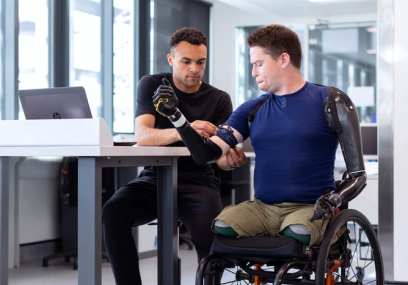 man in wheelchair being fitting for robotic arm