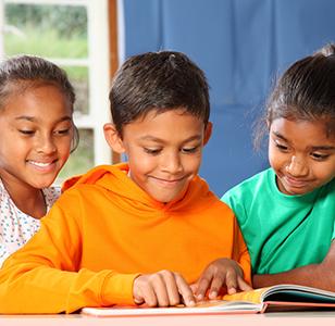 three children around a picture book