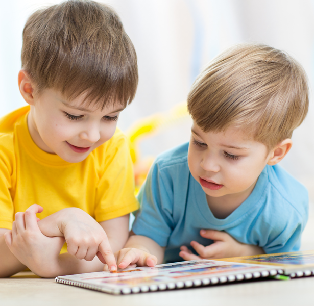 two boys around a picture book