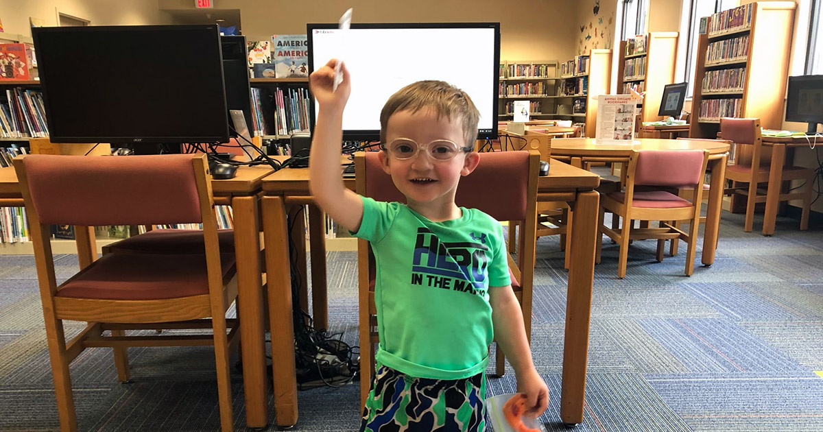 Boy holding library card