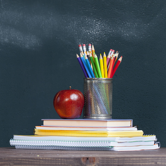 Apple, pencils, books and blackboard