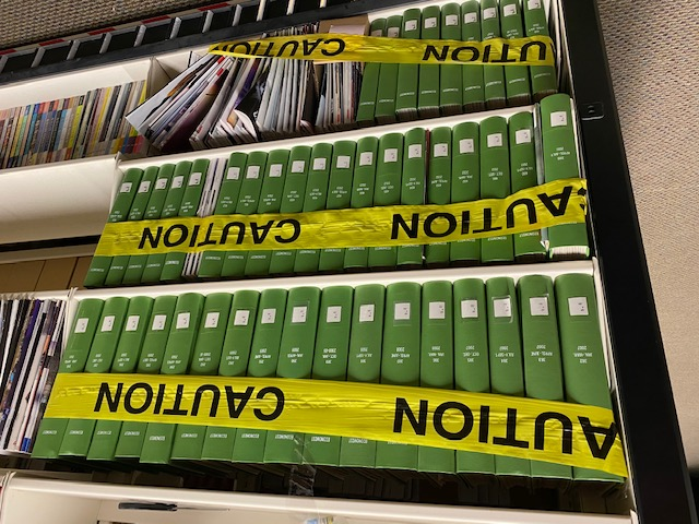 image of caution tape across bound journals to save