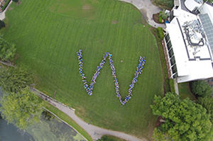Aerial view of staff standing in the shape of a W on Chapel Field