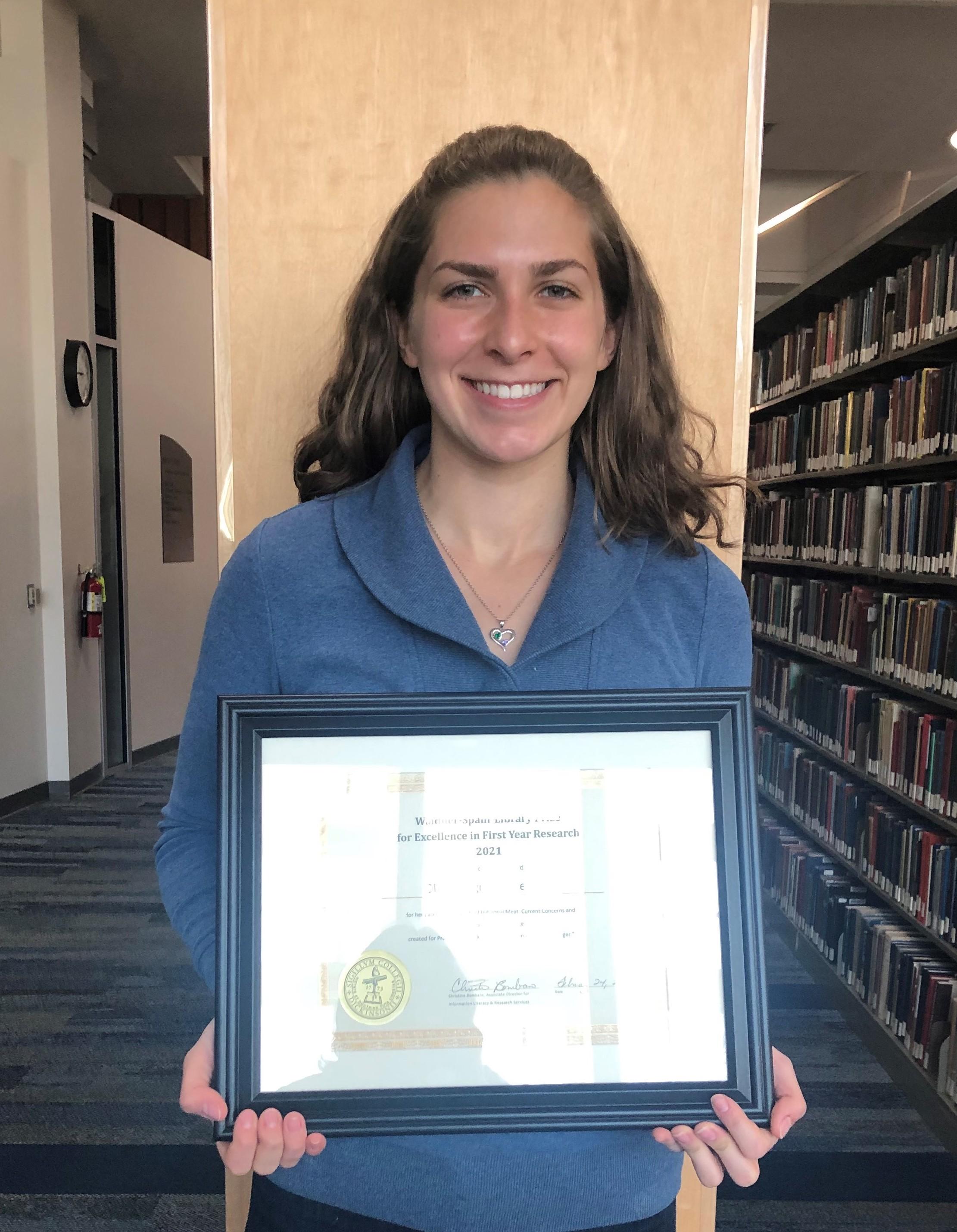 Olivia Oligny-Leggett holding her certificate