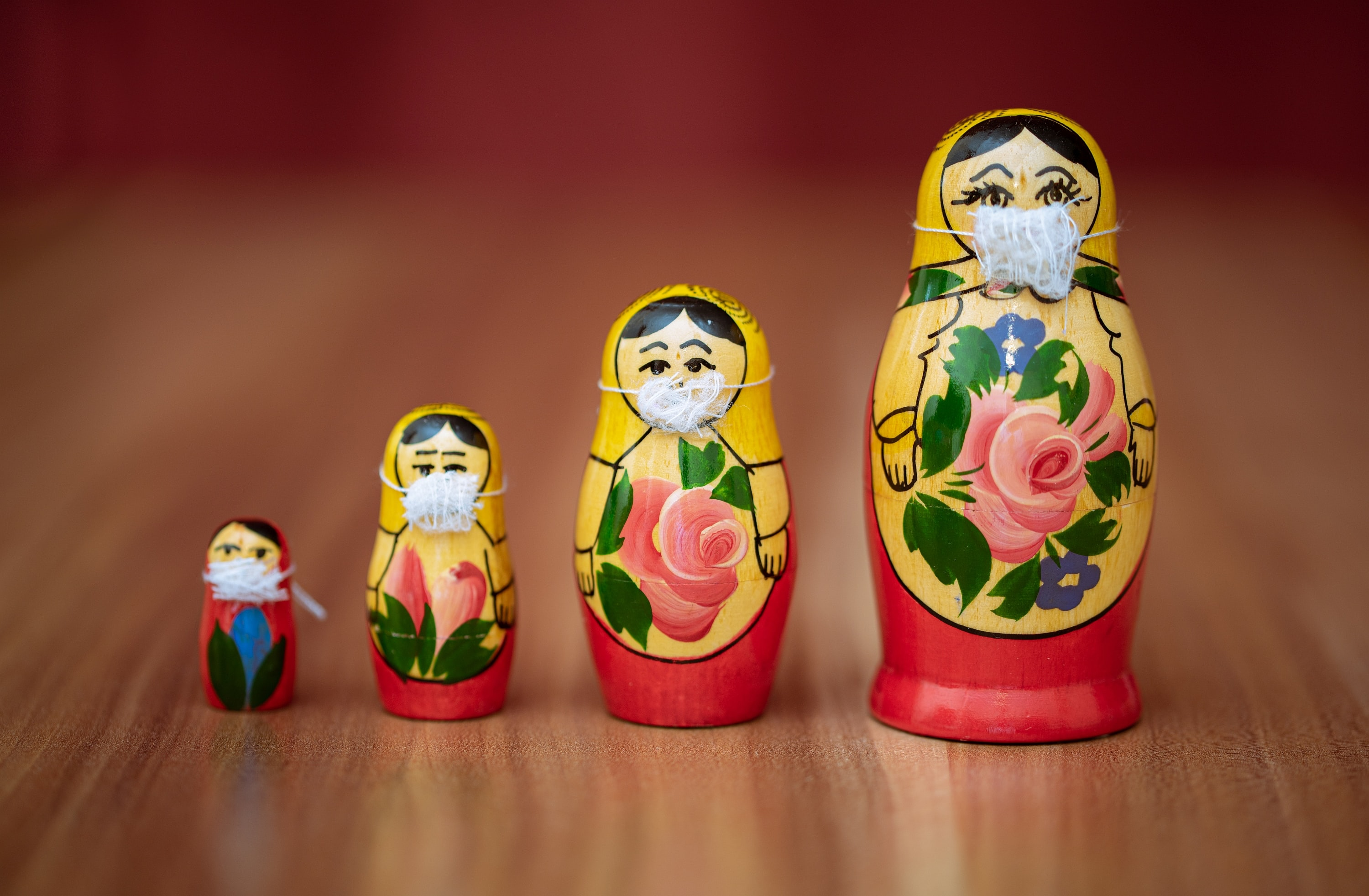 Four Russian nesting dolls wearing medical masks.