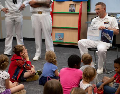 Naval officer in uniform reading a book to kids