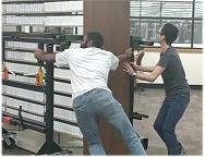two men pushing shelf