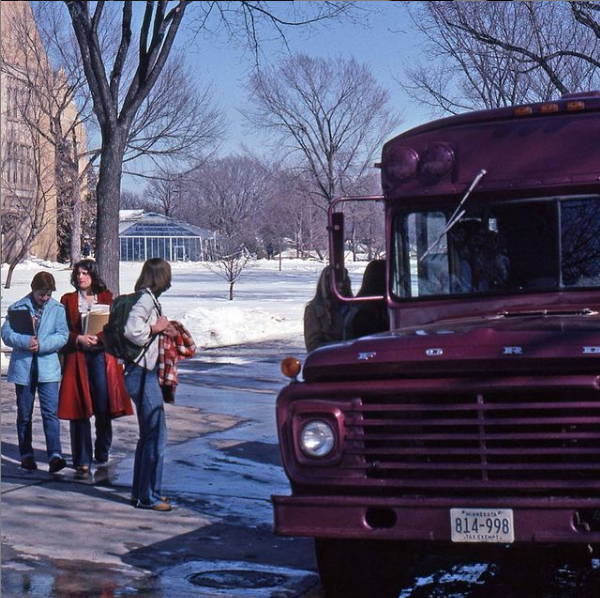 1977: Students line up to get on a purple bus