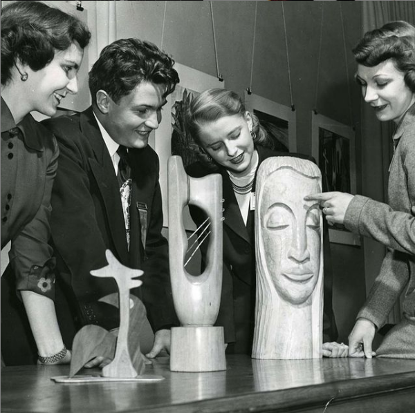 Four students examine a piece of sculpture