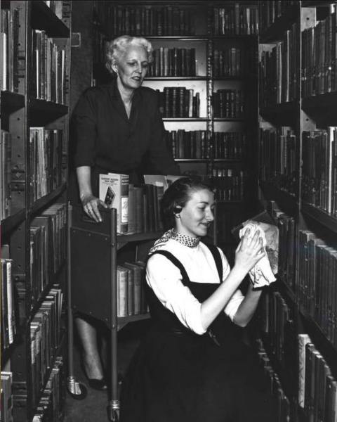 Photo of two librarians shelving books from 1956
