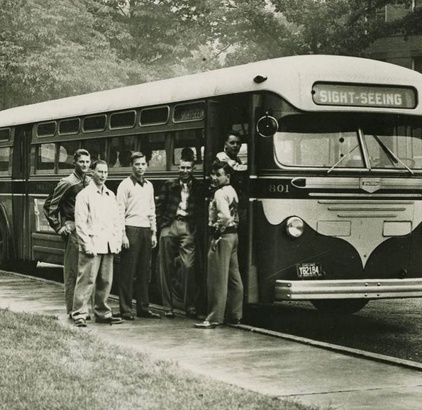 Black and white image of students getting on a bus