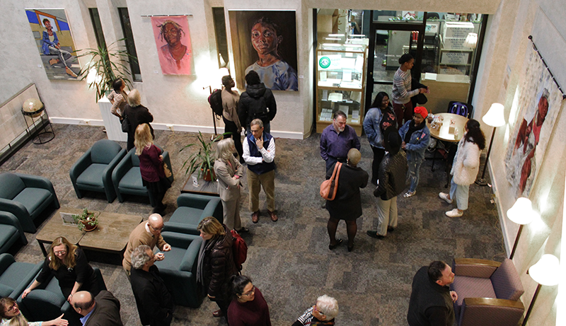 Photograph of Sherrill Library's atrium during a gallery opening. The view is from the from the second floor.