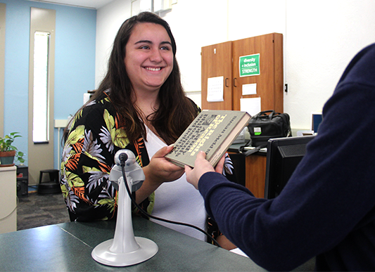 Photograph of student-worker handing a book to a patron at the information desk in Sherrill Library.